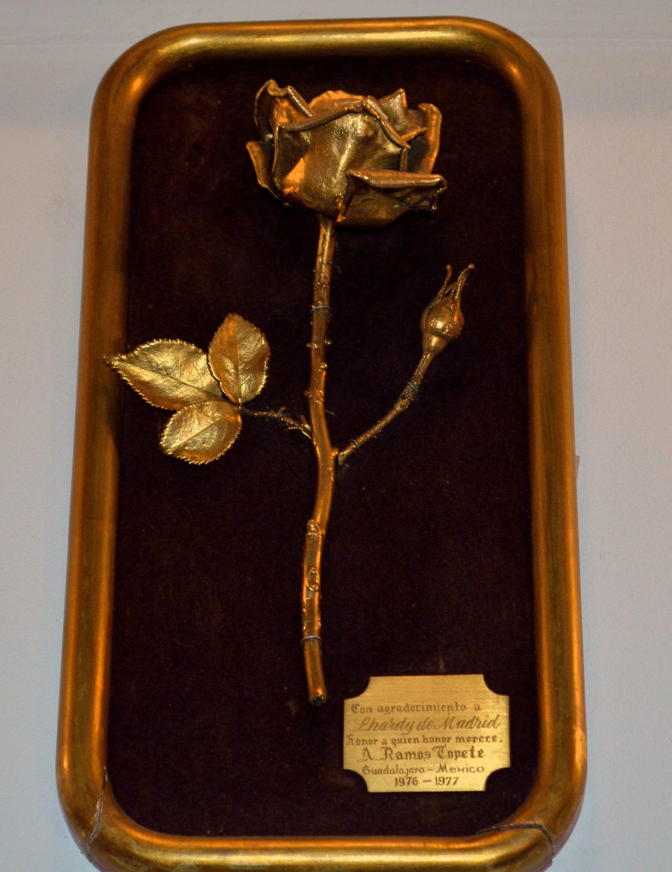 """La rosa que inmortaliza la visita de un mexicano y decora la pared del Lhardy. El señor Ramos Topete, un mexicano de Guadalajara, dejó en Lhardy documentos de gran importancia que le guardaron y le enviaron hasta México en el año 1976, con la leyenda: """"Honor a quien honor merece"""". La rosa es un agradecimiento del jalisciense"""